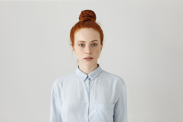 Dipendente femmina bella giovane rossa con crocchia di capelli in posa al chiuso vestito in camicia formale azzurro, prepararsi per il lavoro, avendo un aspetto serio. colpo orizzontale e isolato Foto Gratuite