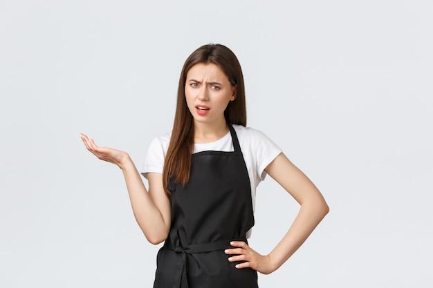 Dipendenti della drogheria, piccola impresa e concetto delle caffetterie. barista femminile scettico infastidito in grembiule nero dicendo così. commessa alzare la mano con sgomento guardando disturbato Foto Premium
