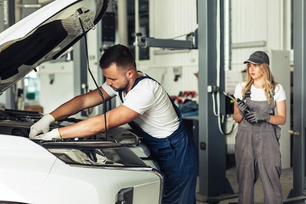Dipendenti di servizio auto vista frontale lavorando Foto Gratuite