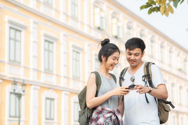 Direzione asiatica delle coppie del viaggiatore sulla mappa di posizione a bangkok, tailandia Foto Gratuite