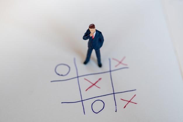 Direzione aziendale e concetto di pianificazione. figura miniatura dell'uomo d'affari che si leva in piedi sulla carta con il gioco del bue Foto Premium