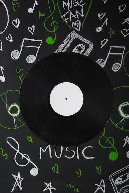 Dischi in vinile sopra la lavagna con note musicali disegnate Foto Gratuite