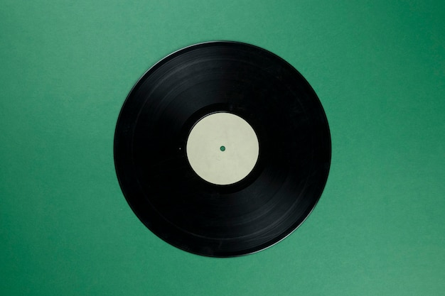 Disco in vinile retrò con etichetta bianca vuota su verde Foto Premium