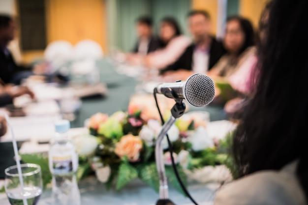 Discorso di altoparlante imprenditrice intelligente e parlando con microfoni in sala riunioni per la conferenza di riunione Foto Premium
