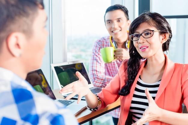 Discussione dei lavoratori dell'agenzia creativa asiatica Foto Premium