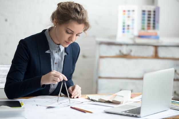 Disegnatore femminile utilizzando la bussola di disegno Foto Gratuite