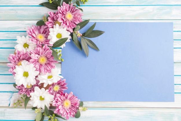 Disegno di fiori decorati su carta bianca sopra il tavolo di legno Foto Gratuite