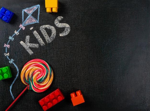 Disegno su carta vetrata. bambini scritti su lavagna e lecca-lecca. spazio copia sfondo. Foto Premium