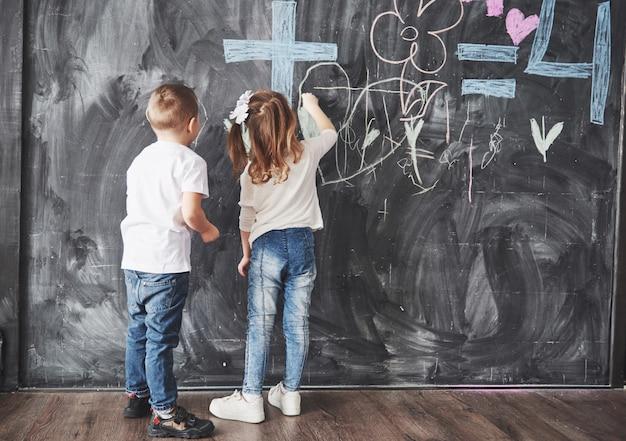 Disegno sveglio del ragazzo e della bambina con il colore del pastello sulla parete. lavoro del bambino. scrittura sveglia dell'allievo sulla lavagna Foto Premium
