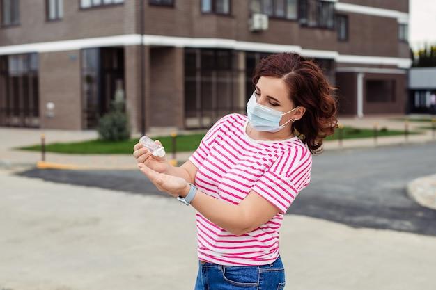 Dispositivi di protezione individuale durante un focolaio di virus. donna in una mascherina medica applica un antisettico per le mani su una strada cittadina Foto Premium