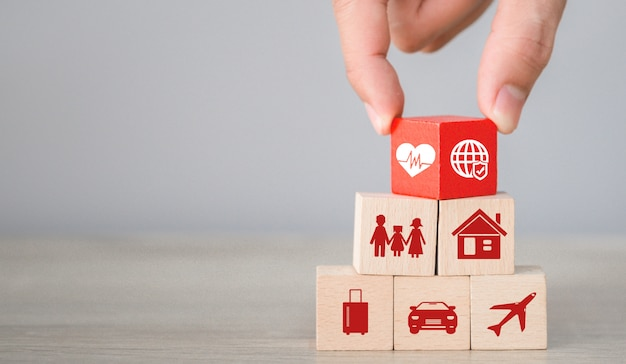 Disposizione a mano di blocchi di legno impilabili con un'icona di assicurazione: auto, Foto Premium