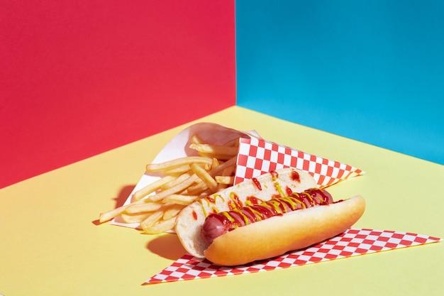 Disposizione ad angolo alto con patate fritte e hot dog Foto Gratuite