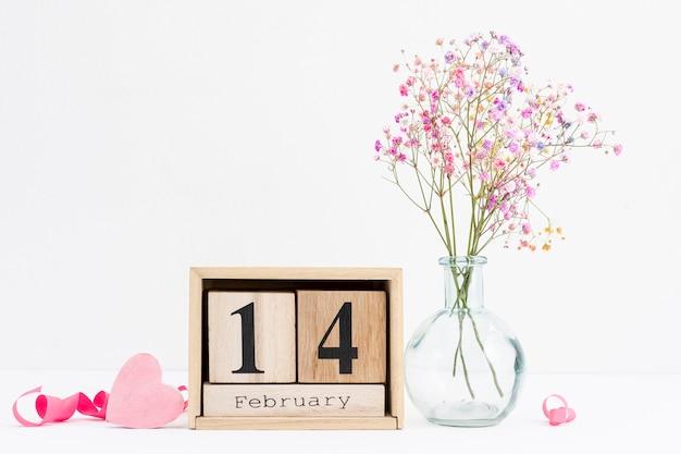 Disposizione con nastro rosa e vaso di fiori Foto Gratuite
