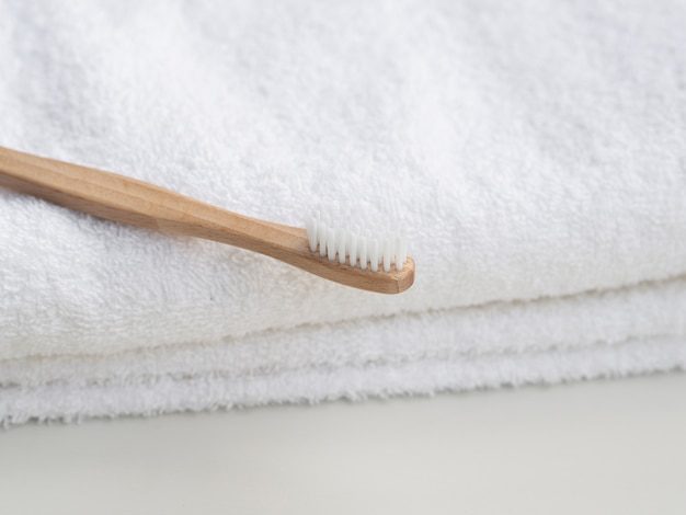 Disposizione con spazzolino da denti in legno e asciugamani Foto Gratuite