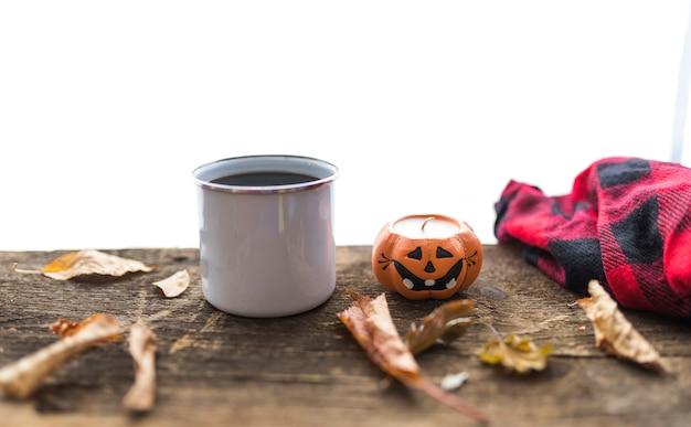 Disposizione con tazza e candela sul tavolo di legno Foto Gratuite