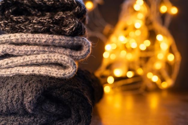 Disposizione con vestiti caldi e luci natalizie Foto Gratuite