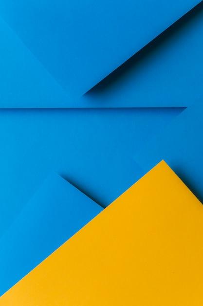 Disposizione creativa di carta colorata di giallo e blu creando uno sfondo astratto Foto Gratuite