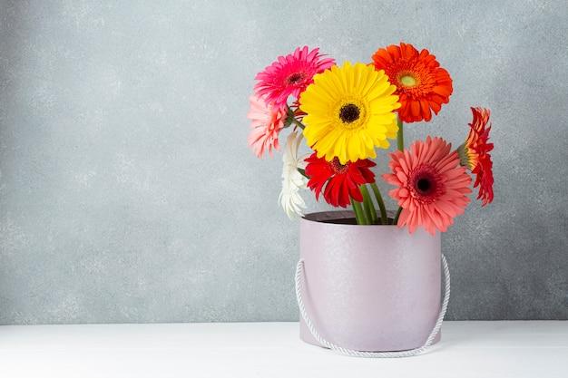 Disposizione dei fiori della margherita della gerbera in un secchio Foto Gratuite