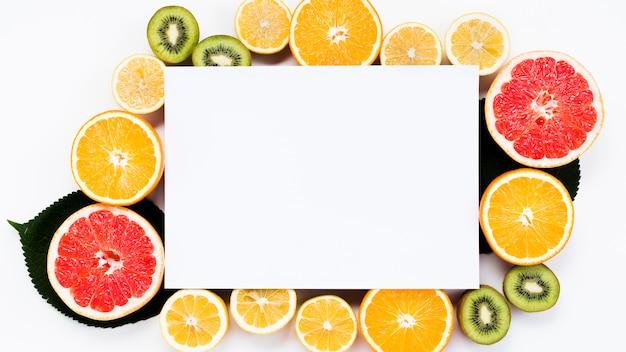 Disposizione dei frutti tropicali colorati a fette con carta bianca Foto Gratuite