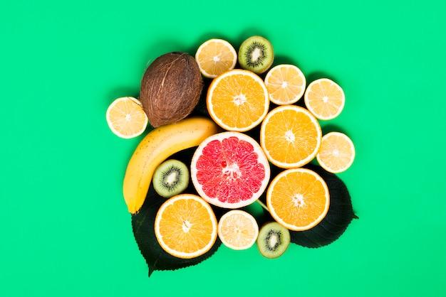 Disposizione dei frutti tropicali colorati misti su sfondo verde Foto Gratuite