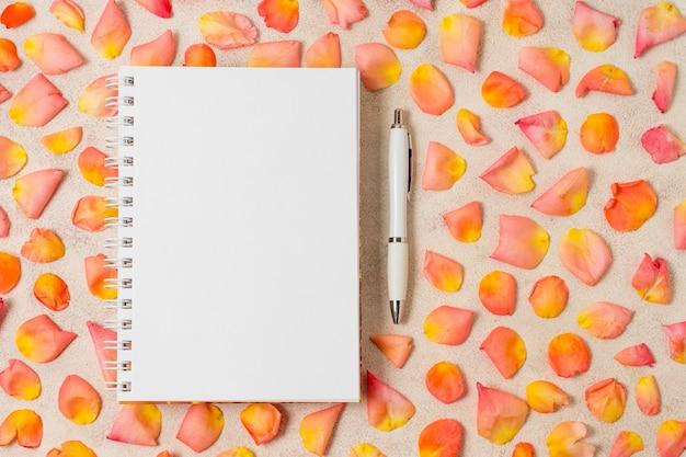 Disposizione dei petali di rosa accanto a un quaderno Foto Gratuite