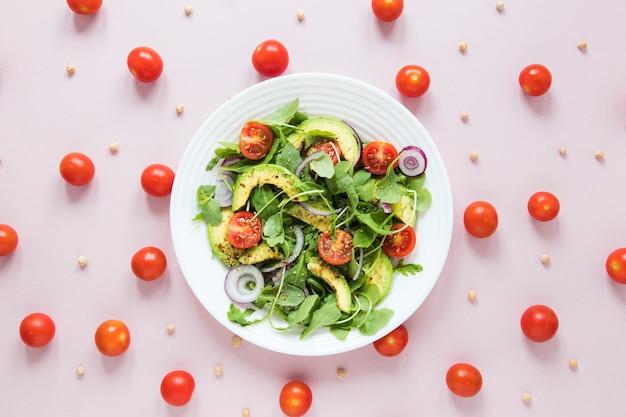 Disposizione dei pomodorini con scodella di insalata Foto Gratuite
