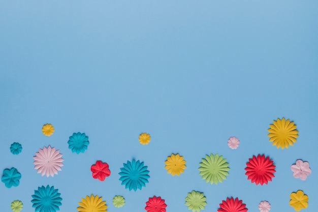 Disposizione del bel ritaglio di fiori su semplice trama blu Foto Gratuite