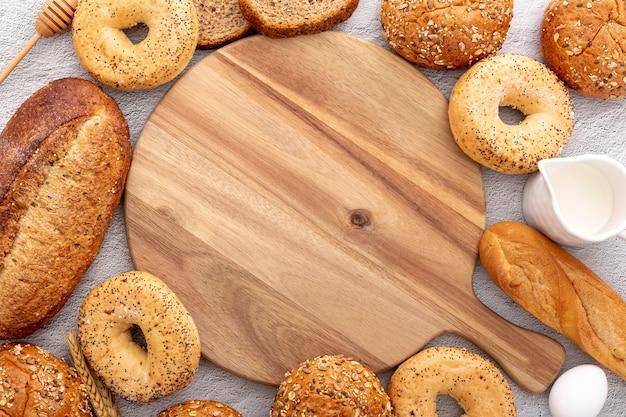 Disposizione del pane che circonda una tavola di legno dello spazio della copia Foto Gratuite