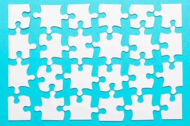 Disposizione del pezzo di puzzle bianco su sfondo blu Foto Gratuite