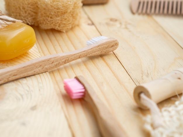 Disposizione dell'angolo alto con le spazzole su fondo di legno Foto Gratuite