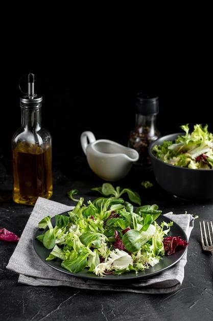 Disposizione dell'insalata di vista frontale con stoviglie scure Foto Gratuite