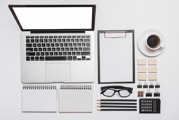 Disposizione della scrivania da ufficio con computer portatile; forniture e tazza di caffè Foto Gratuite