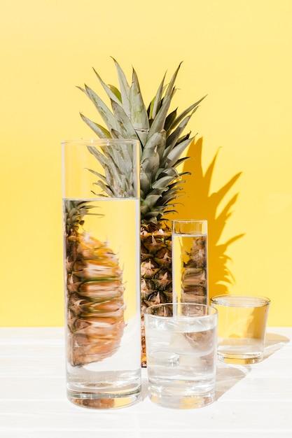 Disposizione di ananas e bicchieri Foto Gratuite