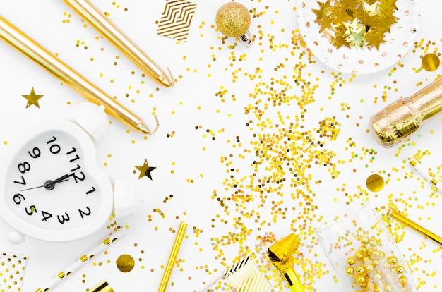 Disposizione di glitter dorati con orologio Foto Gratuite