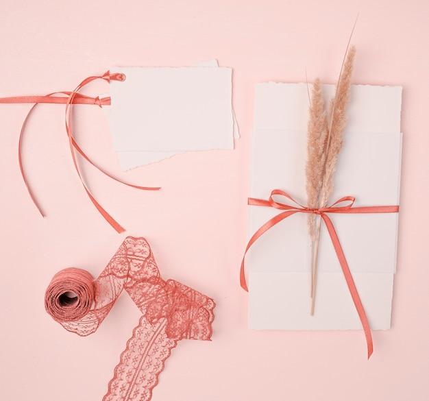 Disposizione girly di vista superiore per gli inviti di nozze su fondo rosa Foto Gratuite