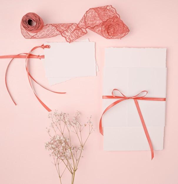 Disposizione graziosa di disposizione piana per gli inviti di nozze su fondo rosa Foto Gratuite