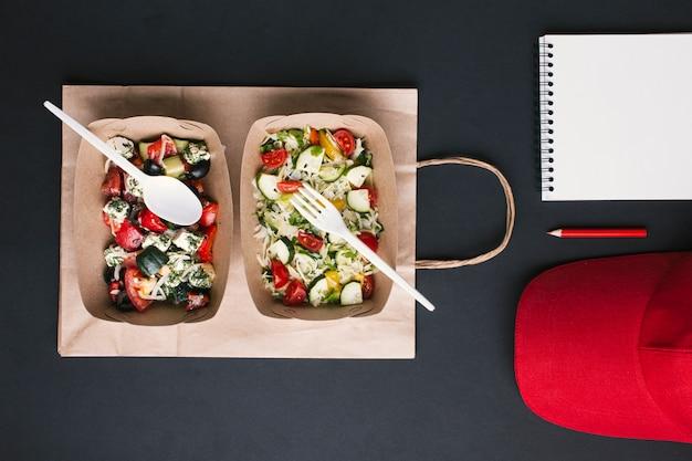Disposizione lat di flay con insalate su sacchetto di carta Foto Gratuite