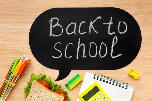 Disposizione piana degli elementi essenziali della scuola con sandwich e taccuino Foto Gratuite