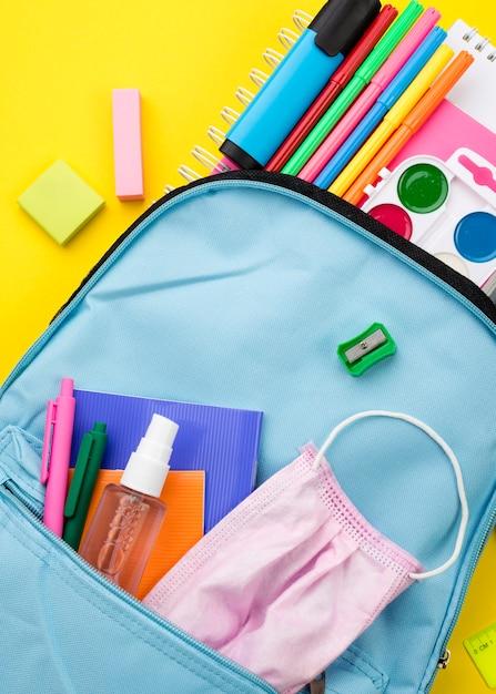 Disposizione piana degli elementi essenziali della scuola con zaino e disinfettante per le mani Foto Gratuite
