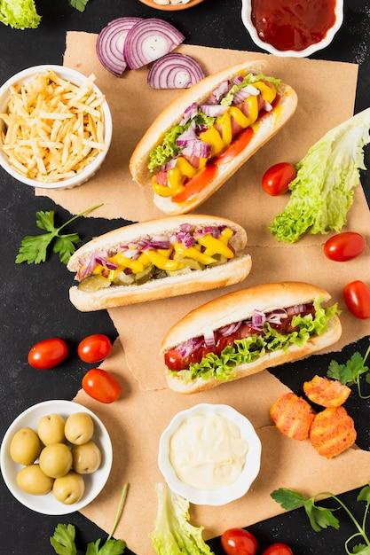 Disposizione piana degli hot dog sulla tabella nera dell'ardesia Foto Gratuite