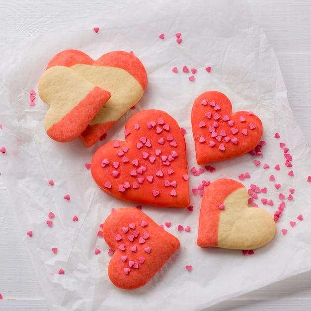 Disposizione piana dei biscotti a forma di cuore su carta Foto Gratuite