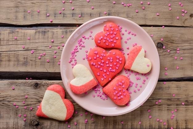 Disposizione piana dei biscotti a forma di cuore sul piatto Foto Gratuite