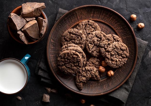 Disposizione piana dei biscotti del cioccolato sul piatto con nocciole e latte Foto Gratuite