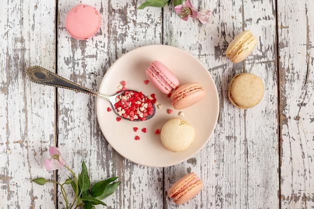 Disposizione piana dei macarons sul piatto con il cucchiaio e i fiori Foto Gratuite