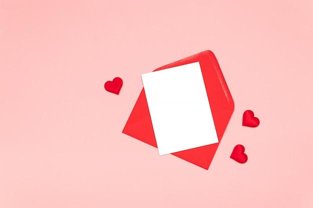 Disposizione piana del concetto dell'iscrizione di amore con le forme rosse del cuore e busta e foglio di carta neri vuoti di carta su una tavola rosa Foto Premium
