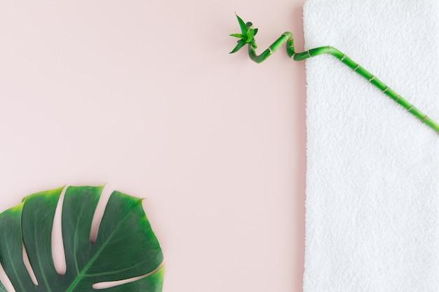 Disposizione piana del concetto della stazione termale con l'asciugamano bianco, il bambù e la foglia di palma, stazione termale con uno spazio per un testo, flatlay Foto Premium