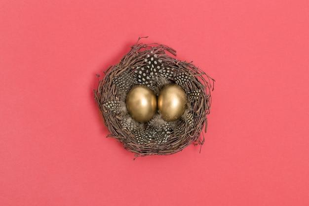 Disposizione piana del fondo rosa di corallo dorato delle uova di pasqua Foto Premium