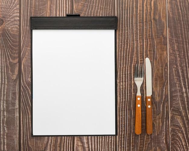 Disposizione piana del menu in bianco su superficie di legno con le posate Foto Gratuite