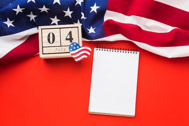 Disposizione piana del taccuino con la bandiera americana e la data Foto Gratuite