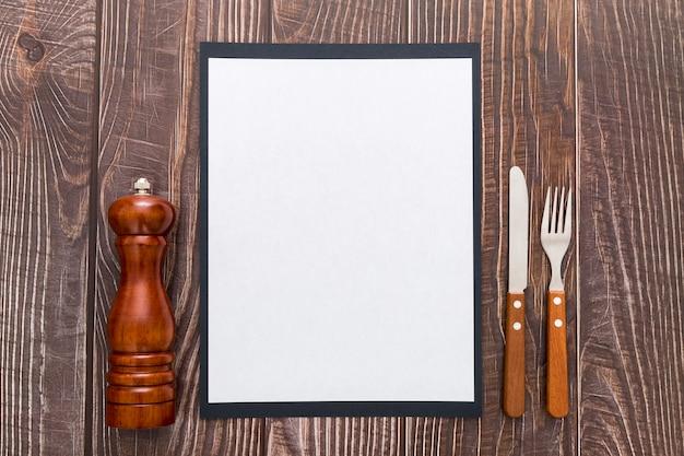 Disposizione piana della carta in bianco del menu con la coltelleria su superficie di legno Foto Gratuite
